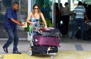Fernanda Lima desembarca no aeroporto cheia de malas e recebe ajuda