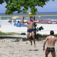 Márcio Garcia, de sunga, joga futevôlei na praia da Barra, no RJ, e se refresca tomando banho de balde e mangueira, em 3 de março de 2013
