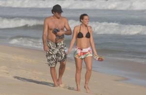 Luciano Szafir passeia com a mulher, que exibe barriga de grávida em praia