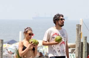 Bruna Linzmeyer e o marido tomam água de coco enquanto se exercitam em praia
