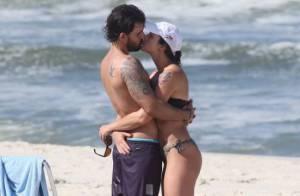 Juliano Cazarré namora a mulher e brinca com o filho na praia da Barra, no Rio