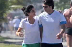 Vanessa Giácomo caminha com o marido, Giuseppe Dioguardi, na orla da praia