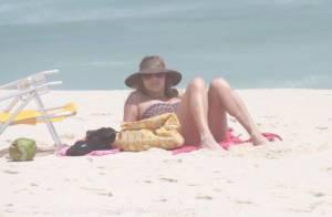 Christine Fernandes lê revista e mostra boa forma em praia carioca