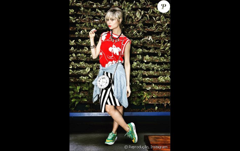 Maria Luiza usou saia assimétrica listrada, blusa jeans amarrada na cintura, tênis Nike e finalizou com a bolsa relógio da Kate Spade