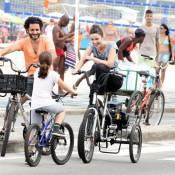 Carolina Kasting passeia de bicicleta triciclo na praia com o marido e a filha