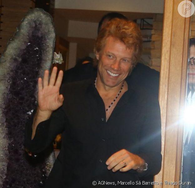 Jon Bon Jovi acena para os fotógrafos ao sair de restaurante em São Paulo neste sábado, 21 de setembro de 2013