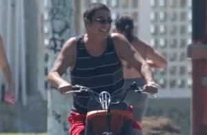 Zeca Pagodinho acena para fotógrafo durante passeio de bicicleta em praia, no RJ