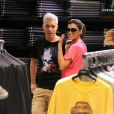 O casal sorri ao perceber paparazzi fora da loja