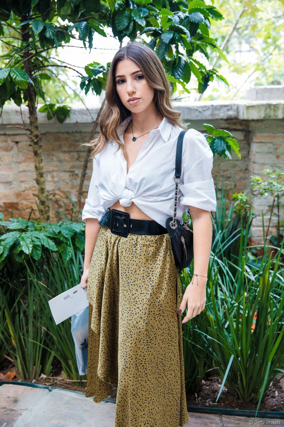 Um cinto largo pode dar um estilo extra ao look com saia e cropped