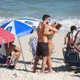 Juliana Paes e o marido, Carlos Eduardo Baptista, se abraçam em praia do Rio enquanto filhos brincam