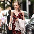 Vestido midi na moda: modelo com estampa floral de fundo preto é tendência