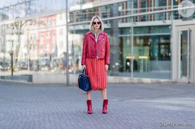 Blusa de moletom por baixo da jaqueta de couro, saia mídi de tecido com botas de couro. A maxibolsa compõe a produção
