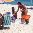 Viviane Araujo passa bronzeador no namorado em dia de praia
