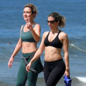 Adriana Esteves caminha, com a barriga de fora, pela orla do Rio