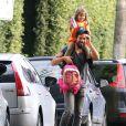 Cauã sorri para fotógrafos caregando a filha, Sofia, nas costas