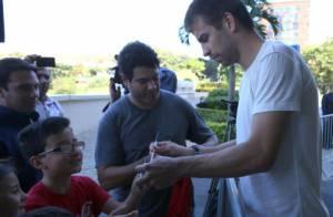 À espera de Shakira, Gerard Piqué distribui autógrafos em porta de hotel no Rio