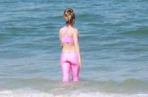 Rita Guedes vai à praia no Rio e entra no mar de calça e top de ginástica