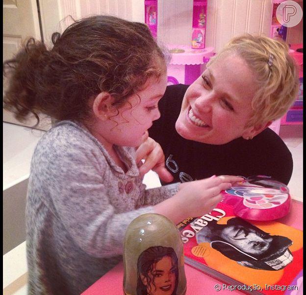 Xuxa brinca com a pequena Maysa, filha de Tânia Mara e do diretor Jayme Monjardim, no quarto da menina, em 25 de junho de 2013