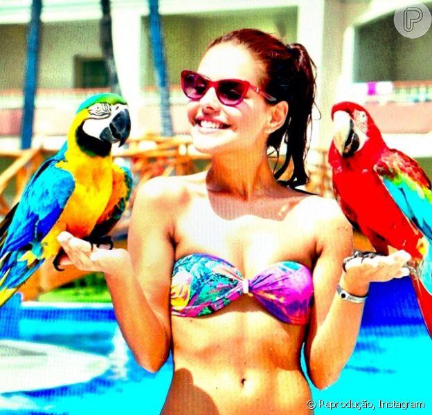 Paloma Bernardi posa de biquíni com duas araras durante férias em Punta Cana, na República Dominicana, em 2 de outubro de 2013