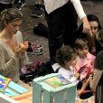 Grazi Massafera observa as unhas enquanto a sua filha, Sofia, brinca com os amiguinhos