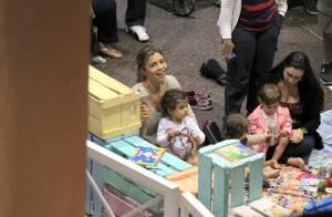Grazi Massafera senta no chão e brinca com a filha, Sofia, em shopping do Rio
