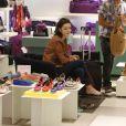 Isabelle Drummond experimenta vários sapatos em dia de compras em shopping do Rio