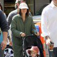 Jennifer Connelly, de boné, casacão e tênis, figurino de sua personagem no longa 'Shelter', no qual interpreta uma moradora de rua, fez um passeio pelo set durante um intervalo das cenas com o marido, o ator Paul Bettany, que a dirigiu no trabalho, e a filha do casal, Agnes, em setembro de 2013