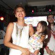 Sheron se diverte no palco com a sobrinha Manuela no colo