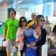 Giovanna Ewbank embarca sorridente com a filha, Títi, no colo no aeroporto Santos Dumont
