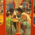 Juliana Paes observa o filho desenhar no parquinho do shopping