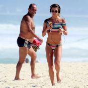 Namorada de Cauã Reymond atrai olhares ao correr de biquíni em praia do Rio