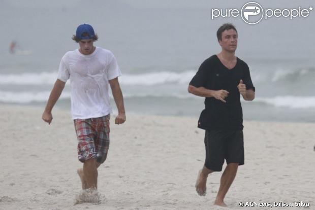 Kayky Brito corre com amigo nas areias da Barra da Tijuca, em 17 de janeiro de 2013