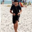 Cauã Reymond corre sozinho ouvindo música em praia