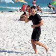 Cauã Reymond acena para fotógrafo durante corrida em praia
