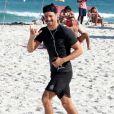 Cauã Reymond acena para paparazzi ao correr em praia da Barra da Tijuca, no Rio de Janeiro, em 4 de junho de 2017