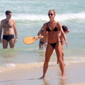 Em dia de sol, Fernanda de Freitas joga frescobol, surfa e namora na praia
