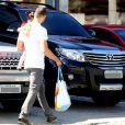 Cauã Reymond caminha até o seu carro com Sofia no colo
