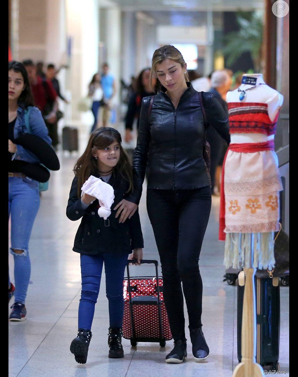 Looks das famosas no aeroporto: Grazi Massafera escolhe skinny em look total black, com jaqueta de couro e tênis para viajar com a filha Sofia, bem prática