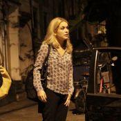 Claudia Abreu senta em banquinho na calçada e se diverte com amigos no Rio