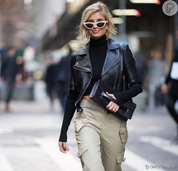 É trendy: óculos escuros estilosos, top e calça cropped + couro + sandália alta em plástico e brilhos.