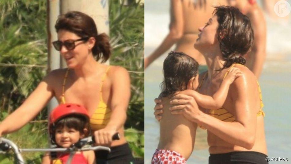 Carol Castro passeou de bicicleta e se refrescou no mar com a filha, Nina, de 1 ano