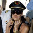 Rihanna pega o chapéu do piloto emprestado para posar na festa que fez com fãs em um avião, em Los Angeles, em 2012