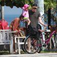 Michel Teló leva a filha Melinda, de 3 anos, no colo até chegar à bicicleta