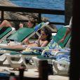 Selena Gomez tomando sol na piscina do hotel Sheraton, no Rio de Janeiro, acompanhada por algumas pessoas da produção do show. A cantora usa um biquini tomara que caia estampado