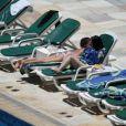 Selena Gomez toma sol na piscina do hotel Sheraton, no Rio de Janeiro, e desamarra a parte de cima do biquini tomara que caia para bronzear as costas