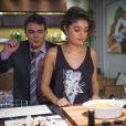 Ao lado de Evandro (Cássio Gabus Mendes), Alice prepara mesa de jantar com blusa soltinha, preta