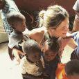 Giovanna Ewbank posa rodeada de crianças em ONG na África
