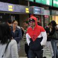 Caio Castro caminha pelo aeroporto parecendo estar mal-humorado