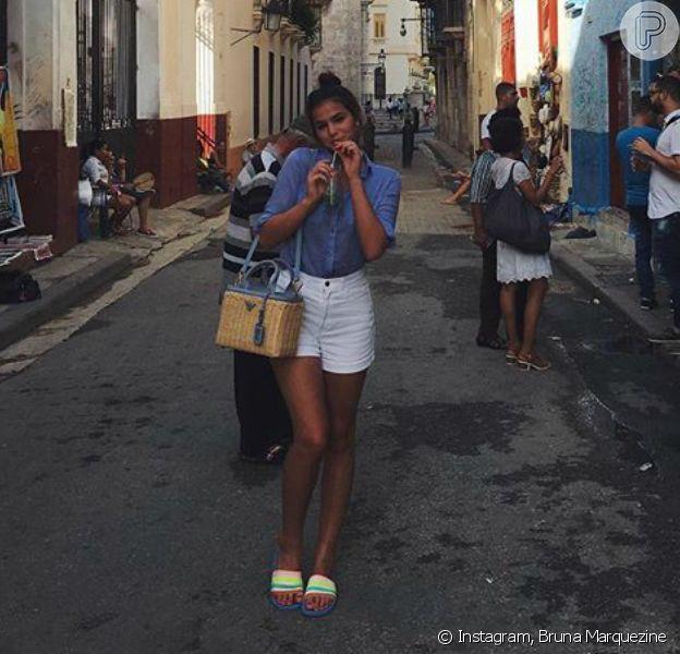 Bruna Marquezine está em Cuba para realizar uma matéria para uma revista e tem esbanjado looks incríveis! Para tomar um mojito no La Bodeguita Del Medio nesta terça-feira, 19 de julho de 2016, a atriz apostou numa camisa Ralph Lauren, short American Apparel, bolsa Prada e chinelos Adidas