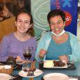 Claudia Rodrigues implorou pela vida da filha, Isa, de 14 anos. Na foto, elas e a empresária, Adriane Botelho, comemoram o aniversário da humorista. 'O outro (bandido) falou 'começa pela pequena. Cala a boca, garota. Você vai morrer!', lembrou a empresária
